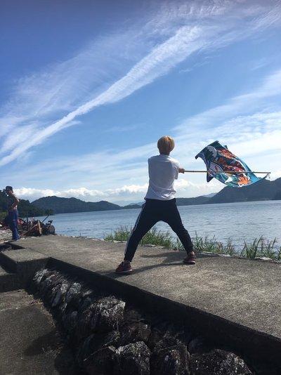 沖島で旗をふる学生